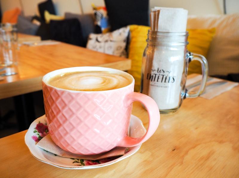 tasse de café latte sur table en bois au restaurant Les Entêtées